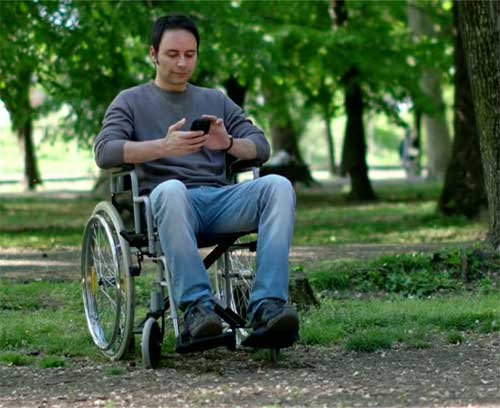 Gentleman in a wheelchair using a smartphone dating app in a park.
